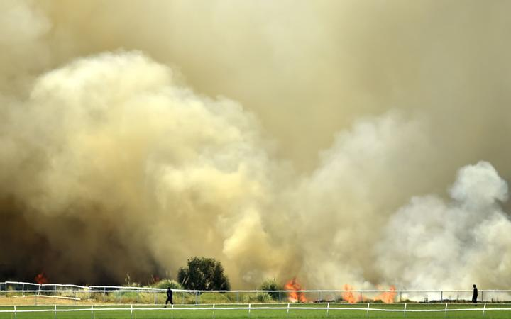 A bushfire burns outside the Perth Cricket Stadium in Perth on December 13, 2019. -