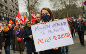 Demonstrators hold sign and flag fron Trade Unions during a demonstration in Lille.