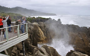 PUNAKAIKI, NEW ZEALAND, MAY 5, 2010: Tourists photograph themselves while the main blowhole is in action at the Pancake Rocks, Punakaiki, West Coast, South Island, New Zealand