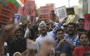 Students and demonstrators hold placards and shout slogans during a protest against India's new citizenship law in Chennai.