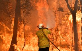 A firefighter conducts back-burning measures to secure residential areas from encroaching bushfires in the Central Coast, some 90-110 kilometres north of Sydney on December 10, 2019.
