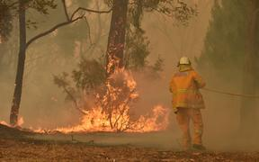 A fireman fights a bushfire to protect a property in Balmoral, 150 kilometres southwest of Sydney on December 19, 2019.