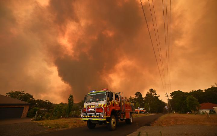 Firetrucks are seen stationed on a road as a bushfire burns in Bargo, southwest of Sydney on December 21, 2019.