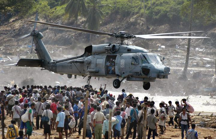 Hundreds of residents of Calang town flock under a US helicopter as volunteers distribute food in Aceh Jaya, in the tsunami-ravaged western Aceh coast, 04 January 2005.