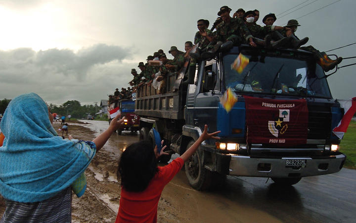 Indonesian refugees ask Indonesian soldiers for food as they pass by their refugee camp in Banda Aceh, 11 January 2005.