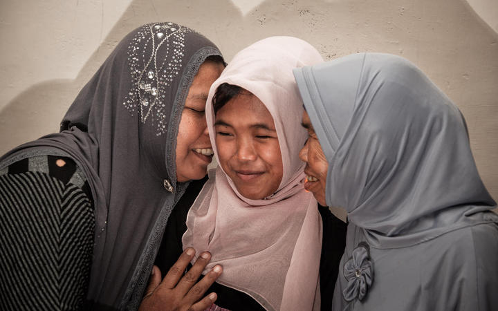 Indonesian mother Jamaliah (left) hugs her daughter Raudhatul Jannah (centre) after they were reunited in Meulaboh, Aceh, Indonesia on August 7, 2014. The girl went missing during the Indonesian tsunami 10 years ago.