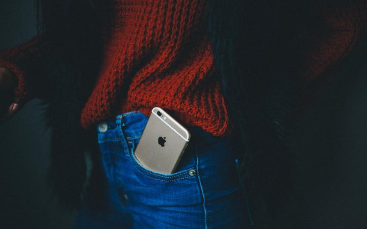 woman with iphone in jeans pocket