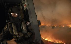 This handout photo taken on December 21, 2019 and obtained on December 22 from the Australia Department of Defence shows an aircrewman monitoring the Tianjara fire from a helicopter in the Moreton and Jerrawangala National Park in Moreton.