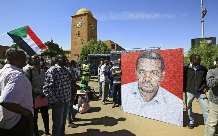 Sudanese protesters rally in front of a court in Omdurman near the capital Khartoum, on December 30, 2019, during the trial of intelligence agents for the death of teacher Ahmed Al-Khair (picture) while in custody of intelligence services.
