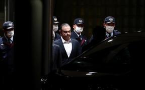 Carlos Ghosn is escorted from the Tokyo detention house after his release.