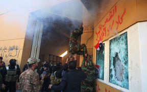 Members of Iraq's Hashed al-Shaabi military network attempt to break into the US embassy in the capital Baghdad, on December 31, 2019.