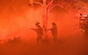 Firefighters struggling against strong winds and flying embers in an effort to secure nearby houses from bushfires near the town of Nowra in the Australian state of New South Wales on 31 December.