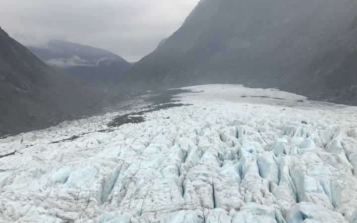 Ice at Fox Glacier seen with some yellowy ash patches on 1 January, 2020, after smoke from Australia's ongoing bushfires drifted across the Tasman.