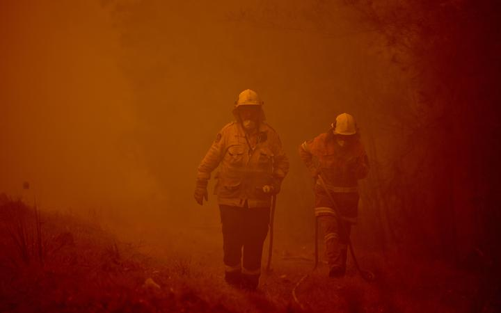 Firefighters tackle a bushfire in the town of Moruya, south of Batemans Bay, in New South Wales.