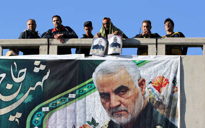 Iranian mourners stand on a bridge during the final stage of funeral processions Qasem Soleimani.