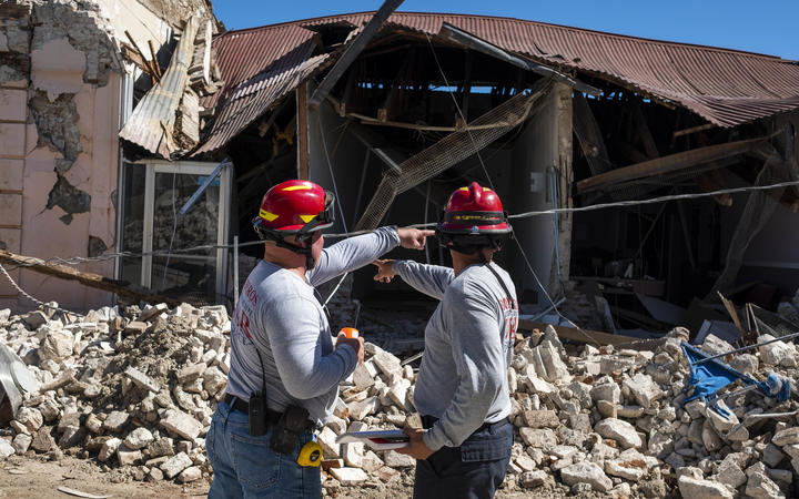 Two firefighters survey a collapsed building after an earthquake hit the island in Guanica, Puerto Rico after a strong earthquake struck early on 7 January, followed by major aftershocks.
