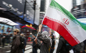 A man holds a Iranian flag during an anti-war protest, at Times Square in New York on January 4, 2020.