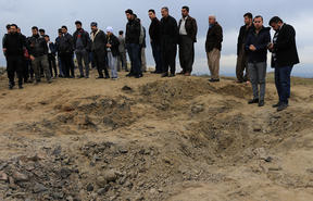 Residents look at a crater caused by a missile launched by Iran on US-led coalition forces on the outskirts of Duhok, Iraq.