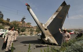 Members of the Iran Revolutionary Guards next to the remains of the plane.