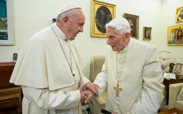 (FILES) This file handout picture taken and released by Vatican Media on December 21, 2018, shows Pope Francis (L) meeting with Pope Benedict XVI (R) at the Vatican.