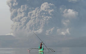 A youth living at the foot of Taal volcano rides an outrigger canoe while the volcano spews ash as seen from Tanauan town in Batangas province, south of Manila, on January 13, 2020.