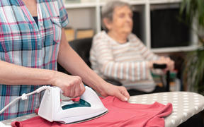 Home, helper ironing clothes for elderly woman.