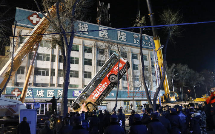 Chinese rescuers watching as a bus is lifted out after a road collapse in Xining in China's northwestern Qinghai province on 13 January, 2020.