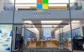 People walk past a Microsoft store entrance with the company's logo on top in midtown Manhattan at the 5th avenue in New York City, US, on 11 November 2019.