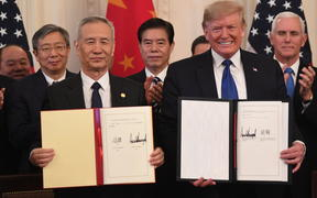 Chinese Vice Premier Liu He and US President Donald Trump display the signed trade agreement between the US and China in the East Room of the White House in Washington, DC, January 15, 2020.