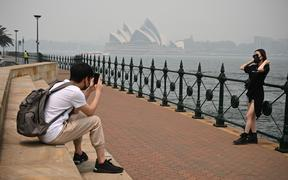 Tourists wearing masks take photos as the Opera House (back, C) is enveloped in haze caused by nearby bushfires, in Sydney on December 10, 2019.