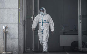 A medical staff member walks outside the Jinyintan hospital, where patients infected by a mysterious SARS-like virus are being treated (January 18, 2020).