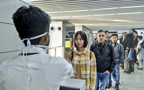 In this handout photograph taken and released by the Ministry of Civil Aviation (MoCA) on January 21, 2020, a man (L) uses a thermographic camera to screen the head of people at Netaji Subhash Chandra Bose International Airport in Kolkata.