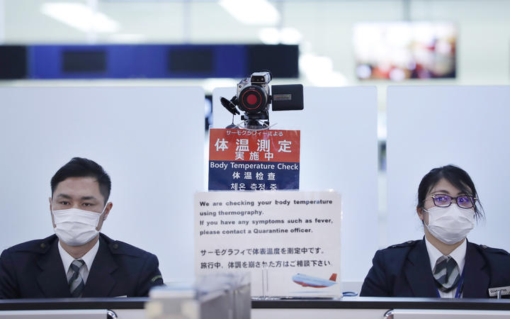 Officers work at a health screening station as they observe passengers arriving on a flight from Wuhan, China, where a SARS-like virus was discovered, at Narita airport, Japan.