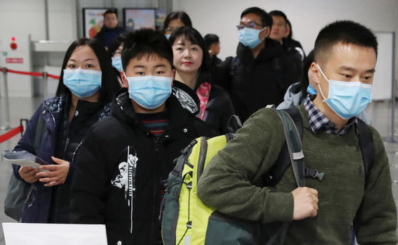 Passengers wearing mask walk at quarantine inspection during the time when a flight arrived from Wuhan at Kansai International Airport in Osaka.