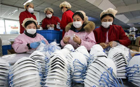 Workers producing face masks at a factory in Handan in China's northern Hebei province, on 22 January 2020.