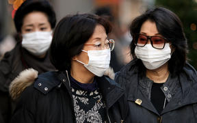People wearing a mask walks past about the outbreak of coronavirus in Wuhan, China at Ginza shopping district in Tokyo, Japan, January 26, 2020.  (Photo by Hitoshi Yamada/NurPhoto)