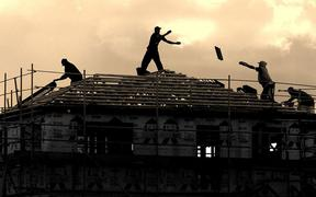 Builders working on the roof of a house.