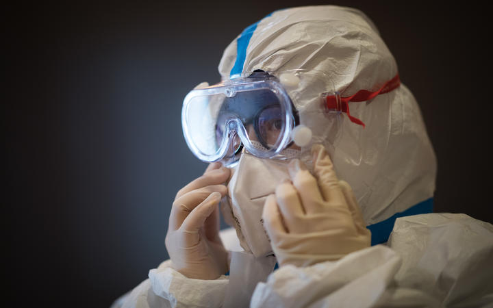 A member of the medical team of the Second Military Medical University puts on protective clothing at Hankou Hospital in Wuhan on 27 January, 2020.