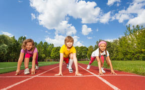 A photo of smiling children on bending knees ready to run a race