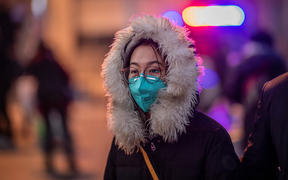 A woman wearing a protective mask walks on the street outside Beijing railway station on January 22, 2020.