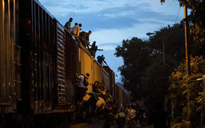 "Undocumented migrants climb on a train known as ""La Bestia""."