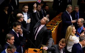 Britain's Brexit Party leader Nigel Farage holds up a small Union Jack in the European Parliament following a vote to ratify the  Brexit deal