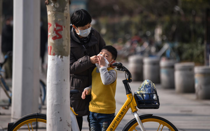 A woman cleans a boy's face in Wuhan,  Hubei province. The number of confirmed cases in the new virus outbreak in China reached 5,974 on 29 January.
