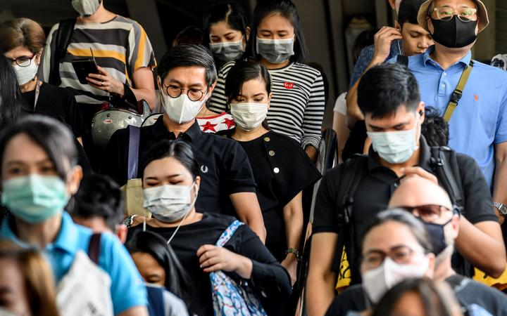 People wearing protective facemasks leave the city commuter train station in Bangkok.