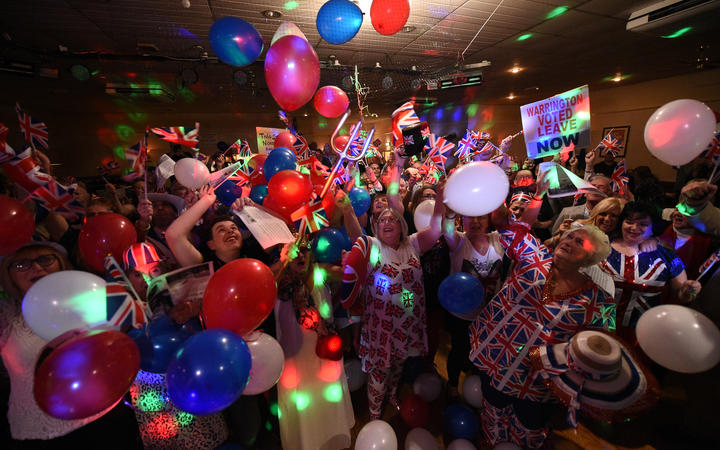 Brexit supporters wave Union flags as the time passes 11 O'Clock at a Brexit Celebration party at Woolston Social Club in Warrington.