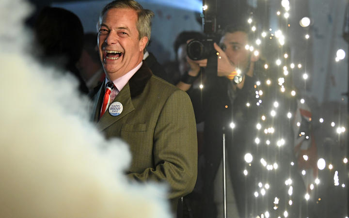 Brexit Party leader Nigel Farage smiles on stage in Parliament Square.