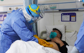 A medical staff member checking a patient infected by the novel coronavirus in an isolation ward at a hospital in Zouping in China's eastern Shandong province.