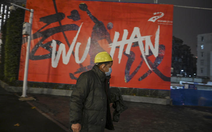 A man wearing a protective facemask walks along a street in Wuhan on 26 Januar, a city at the epicentre of a novel coronavirus outbreak.