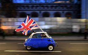 A man waves Union flags from a BMW Isetta as he drives past Brexit supporters gathering in Parliament Square, in central London on January 31, 2020, the day that the UK formally leaves the European Union