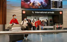 Passengers from international flights at Auckland Airport on Monday 27 January, after flights from Guangzhou and Shanghai had touched down. Some people were wearing masks.